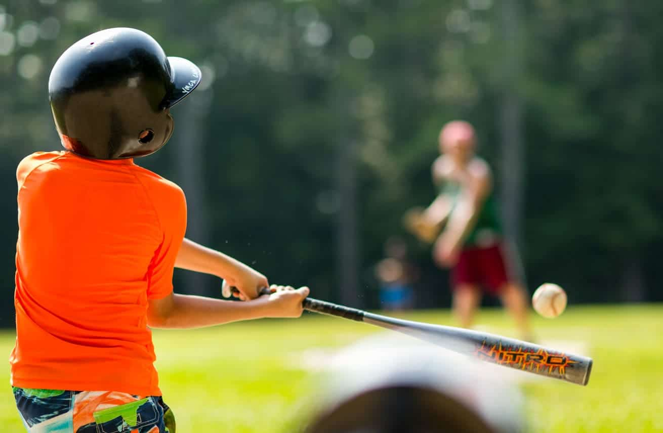 a boy swinging a baseball bat at a ball