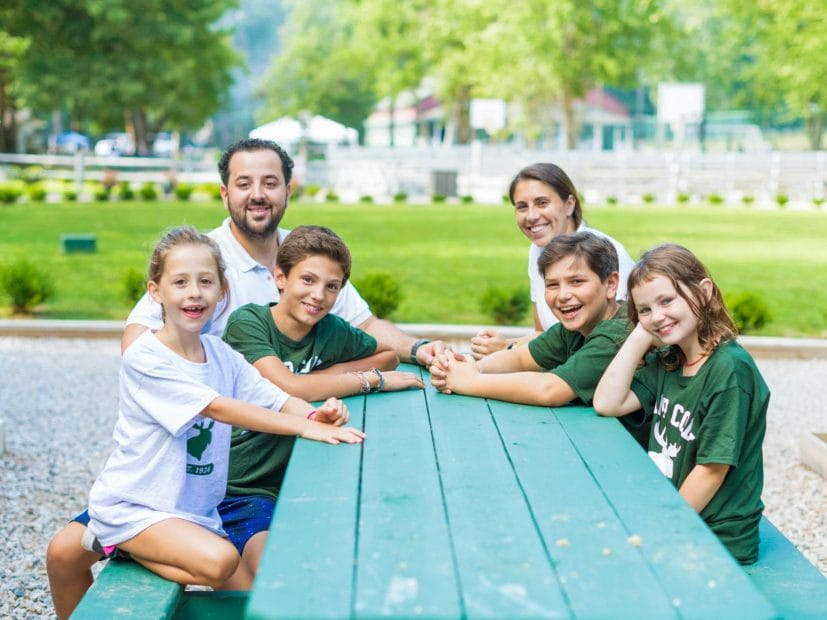 camp directors with kids at a picnic table