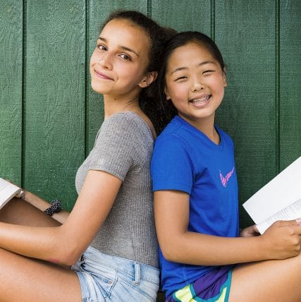 two girls sitting back to back holding books