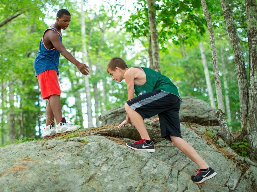 boy climbing a rock while another offers a helping hand