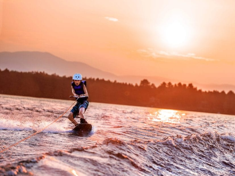 camper wakeboarding at sunset