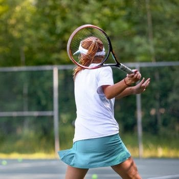 young girl swinging a tennis racket