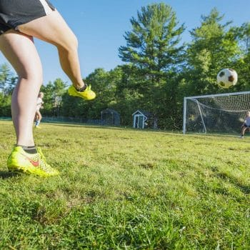 girl kicking a soccer ball into a net