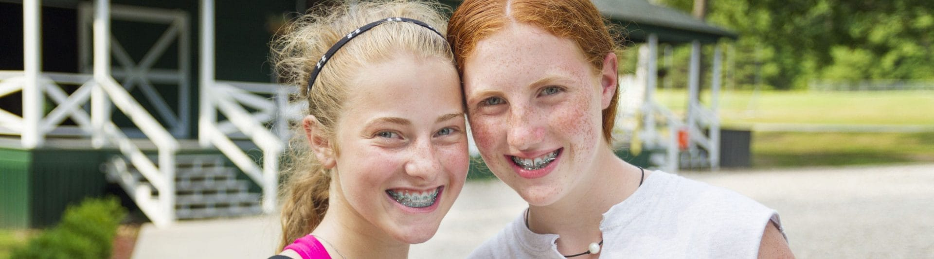 two girls with braces smiling