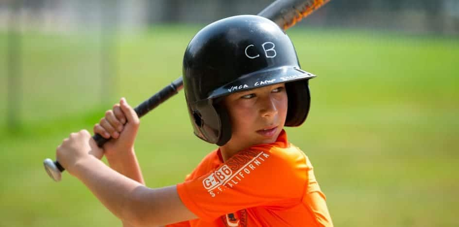 young boy with a baseball bat ready to swing