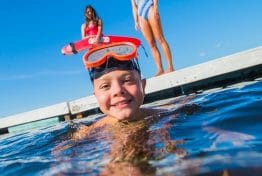 boy with scuba goggles in the water while a lifeguard watches