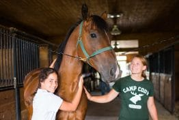 a camper hugging a horse while an instructor pets him