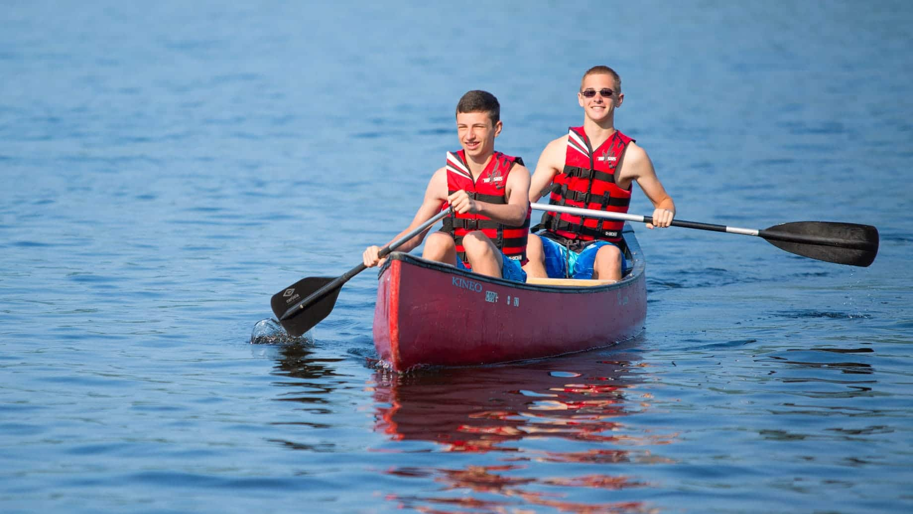 two boy campers paddling a canoe
