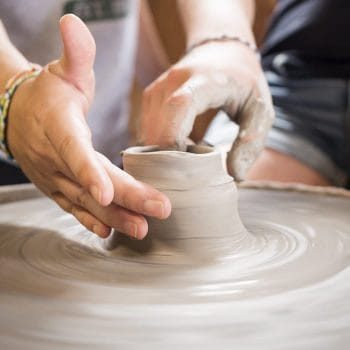 two right hands working to form a ceramic pot