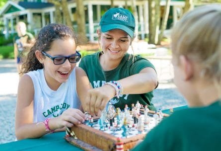 counselor and camper playing chess