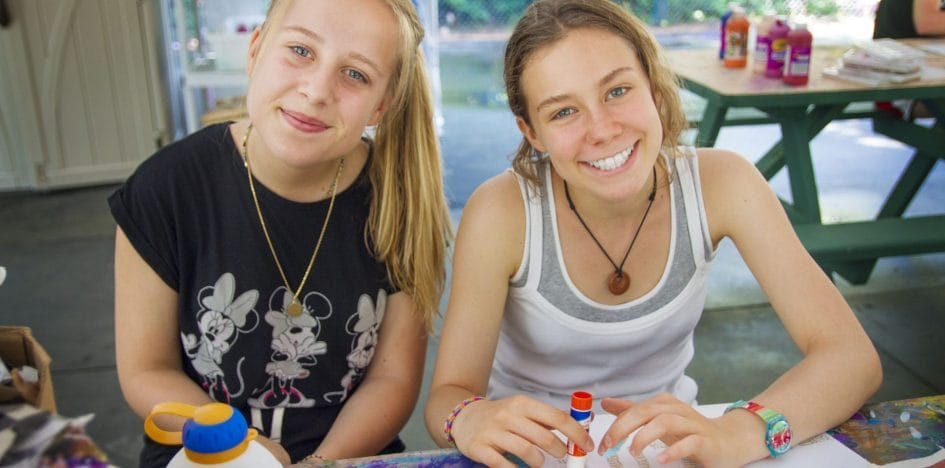girls smiling while gluing