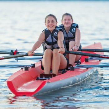 two girls smiling while they row