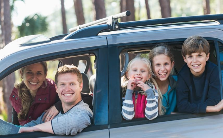 family sticking their heads out of a car