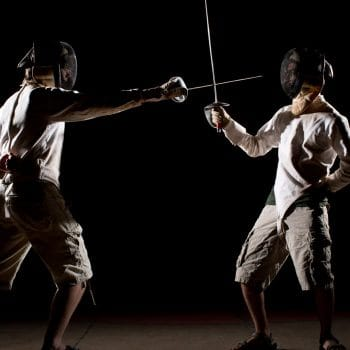 camper in fencing gear parrying with a sabre
