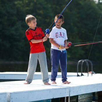 two young boys fishing on a pier
