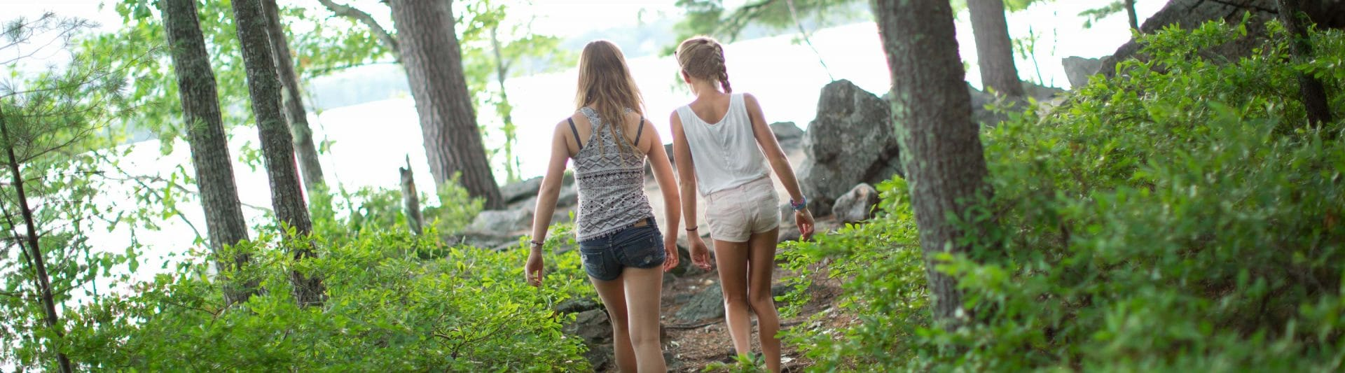 two girls walking down a path in the woods