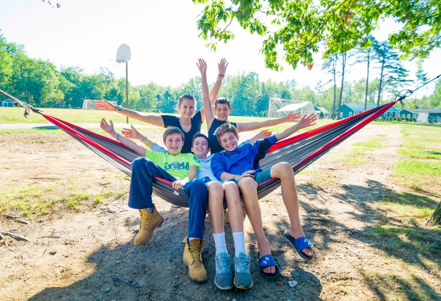 group of boys and one girl relaxing on a hammock