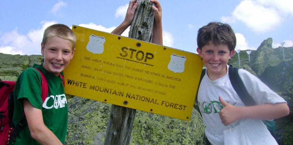 boys smiling next to sign for white mountain national forest
