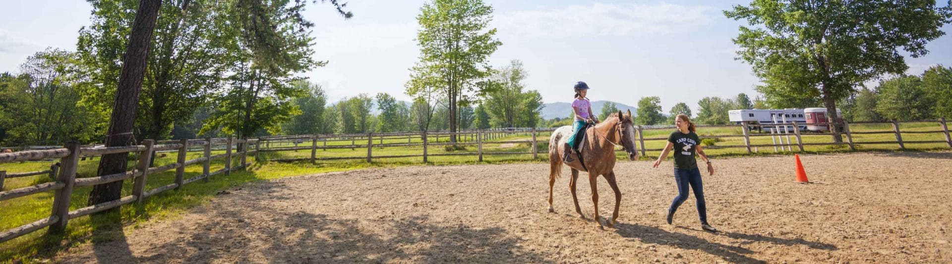 young girl rides a horse while an instructor leads them