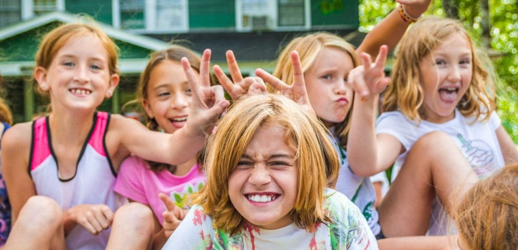 girls at summer camp making bunny ears with hands