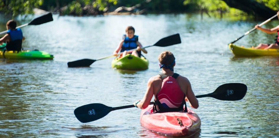 counselor kayaking toward campers