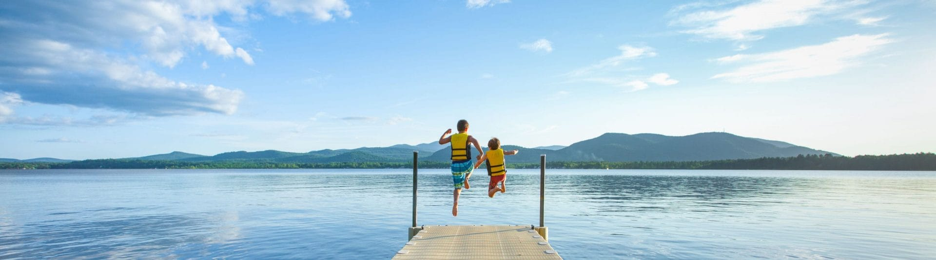 two boys jumping off a pier into a lake