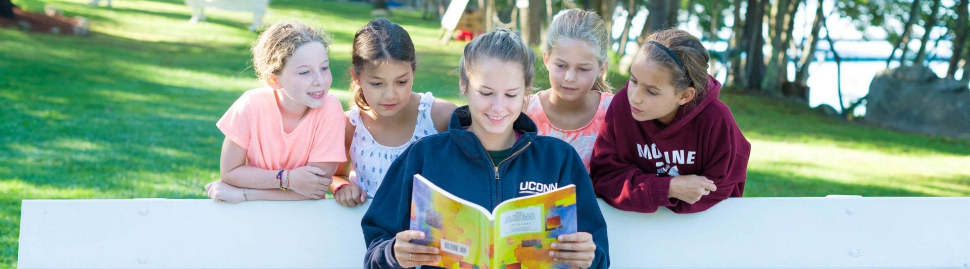 girl counselor reading while four young girls look over her shoulder