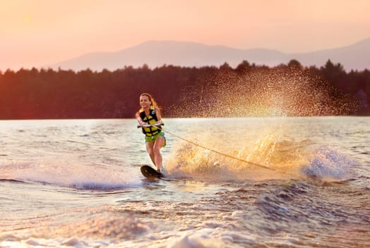 girl wakeboarding at sunset