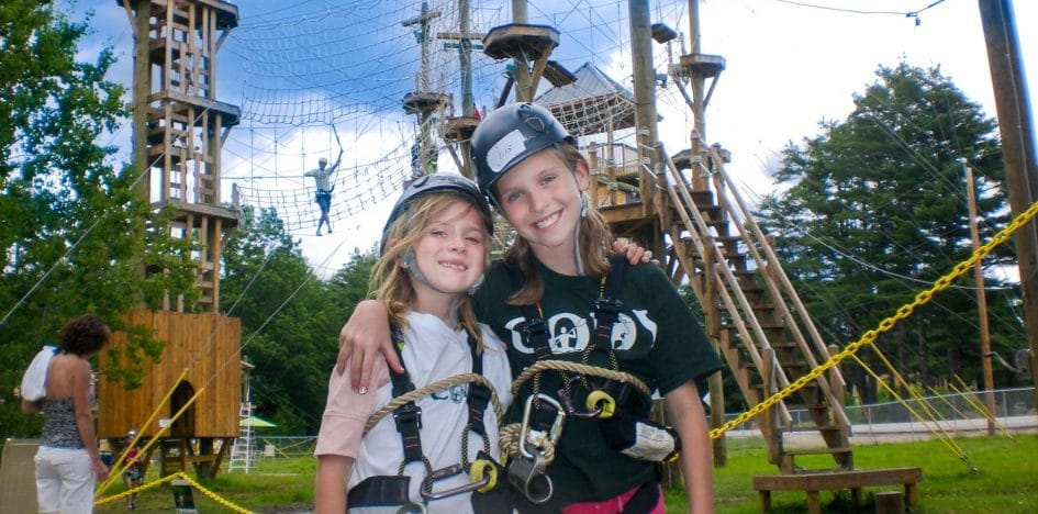 two girls smiling in front of an aerial park