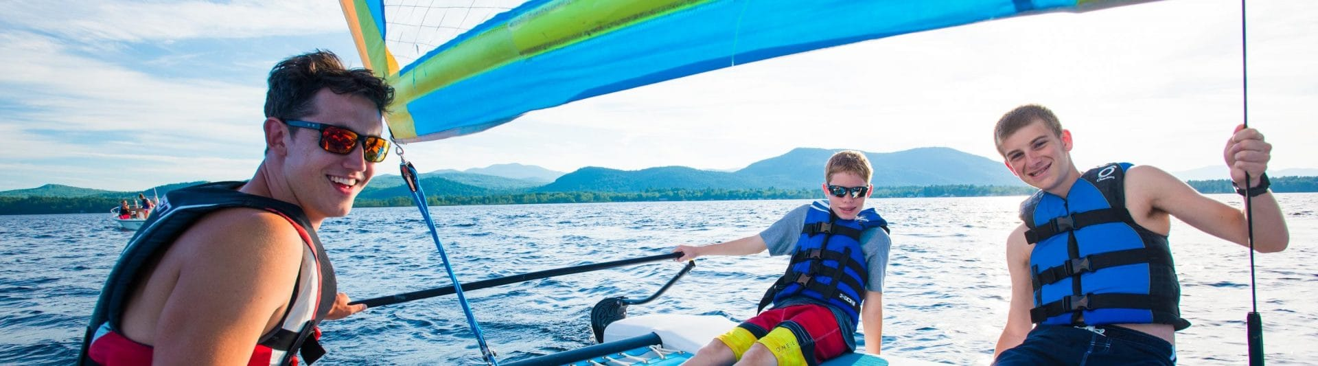 three boys relaxing on a sailboat