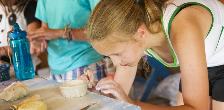 young girl sculpting a pot