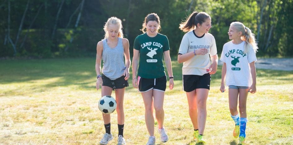 four girls walking with a soccer ball
