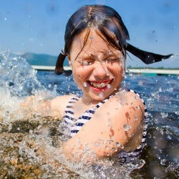 girl smiling and closing her eyes as water is splashing her