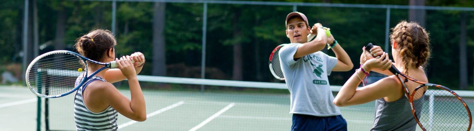 an instructor showing how to do a proper follow through with a tennis forearm swing