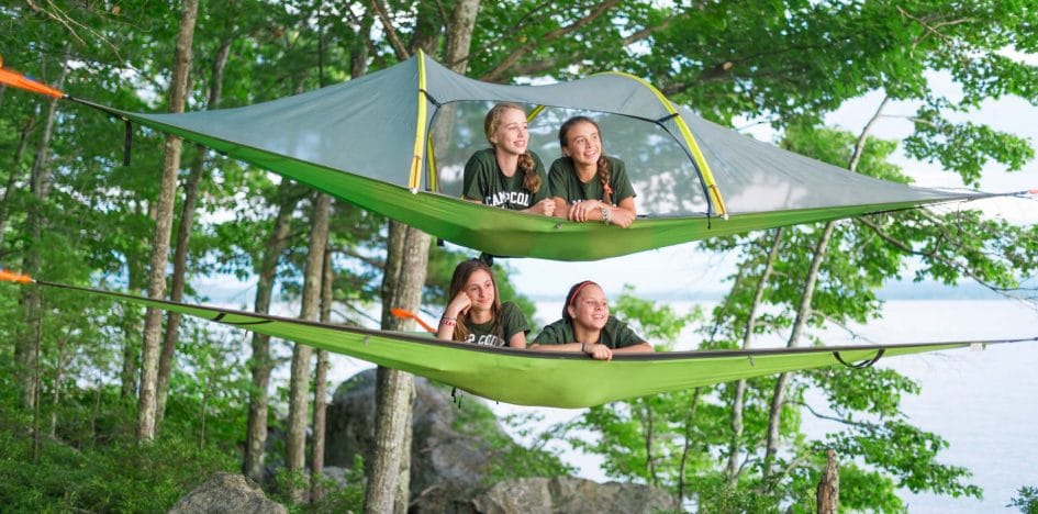 girls relaxing in hammocks above the ground