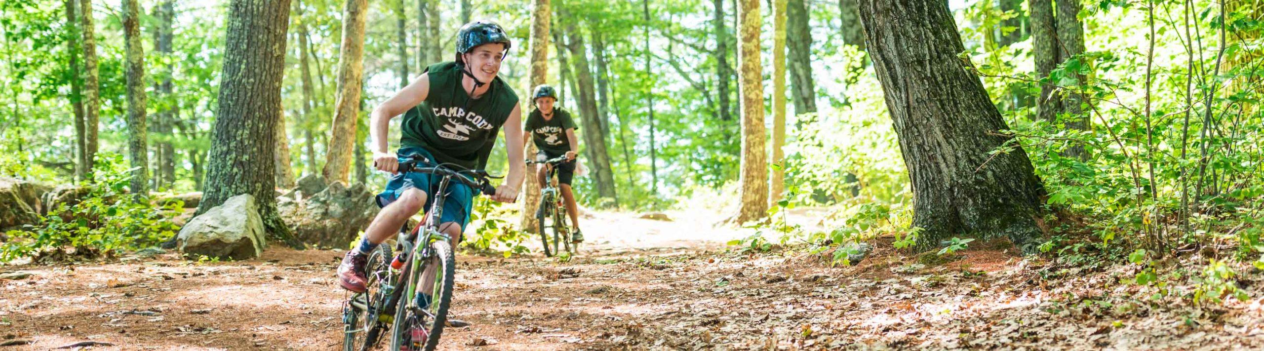 boys riding bikes through the woods