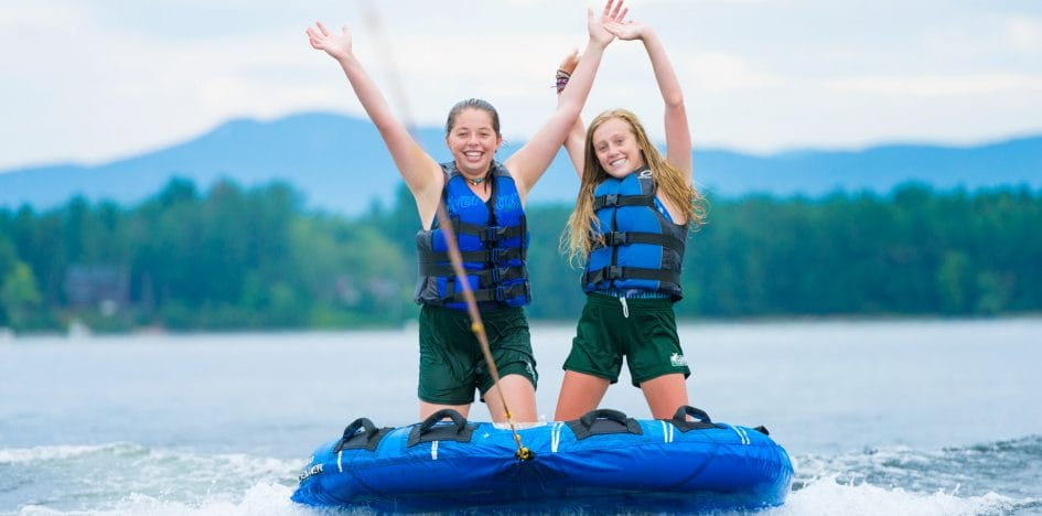 girls raising their hands while riding a water board