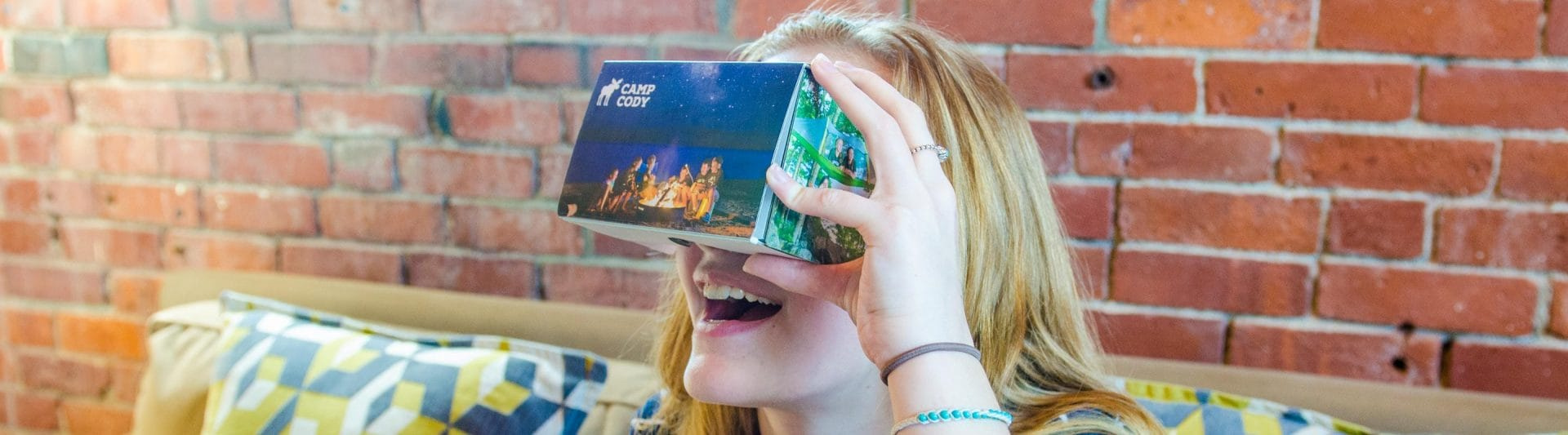 girl smiling while looking at a virtual tour box
