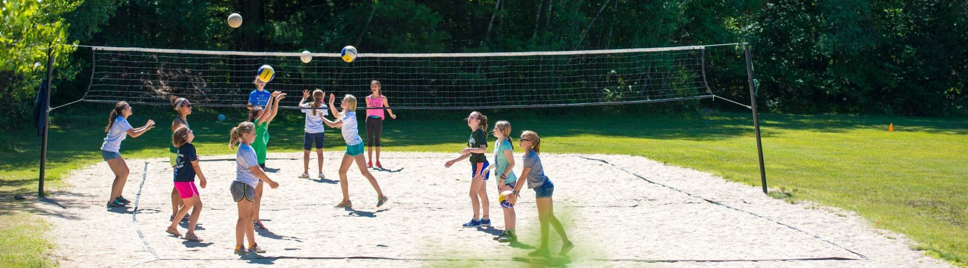 campers playing beach volleyball on a sand court