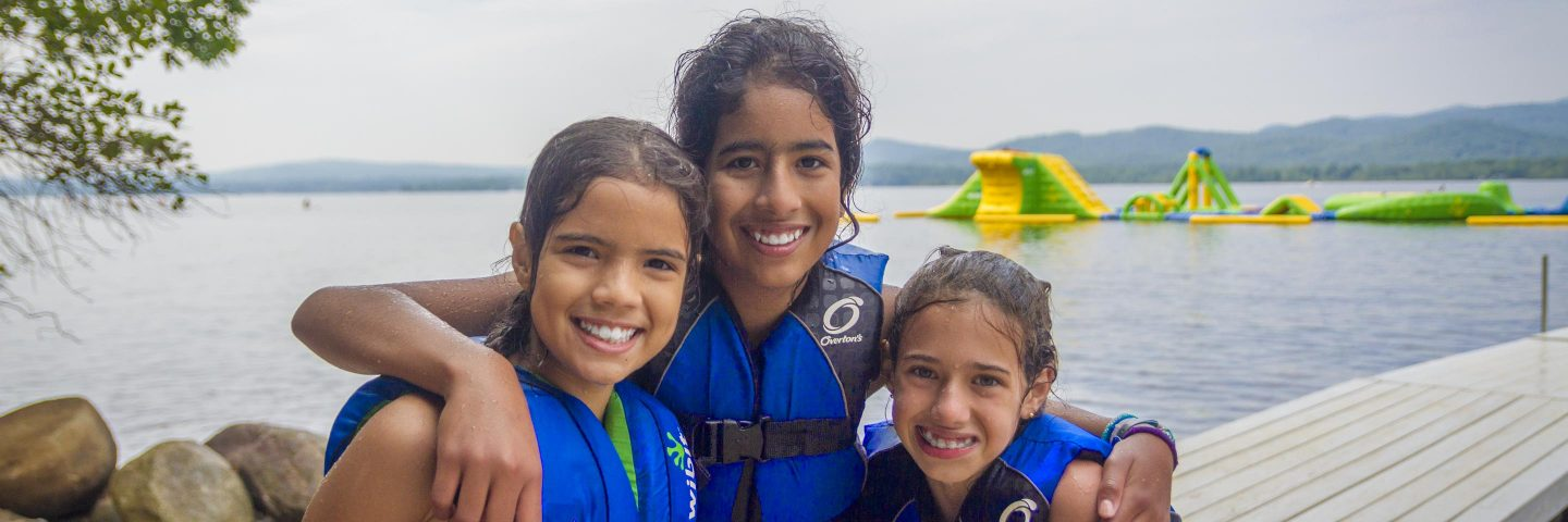 girls at summer camp posing in front of lake