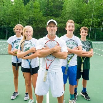 tennis instructor with students, hugging tennis rackets
